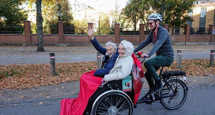 Senior*innen und Radfahrer*innen in einer Rikscha